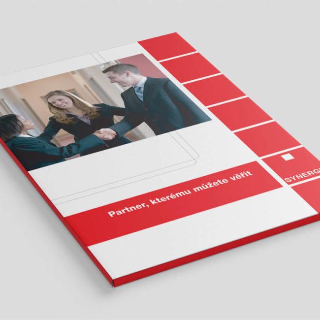 Fotografie červenobílých firemních desek společnosti Synergie s fotografií tří lidí podávajících si ruce.