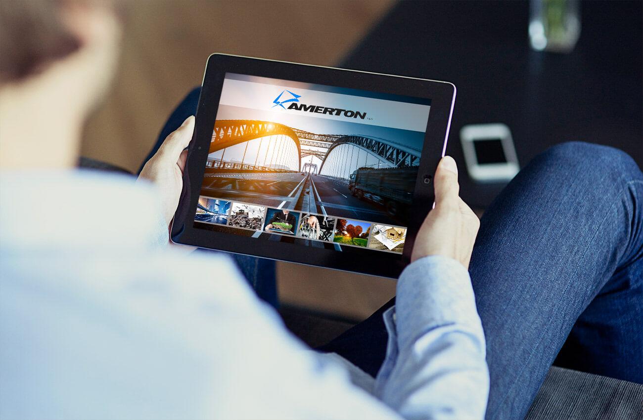 Muž drží iPad, na kterém si prohlíží online prezentaci společnosti Amerton.