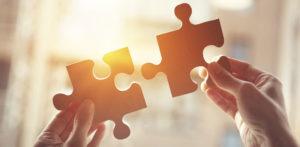 Dvě ruce držící proti světlu dva dílky puzzle.