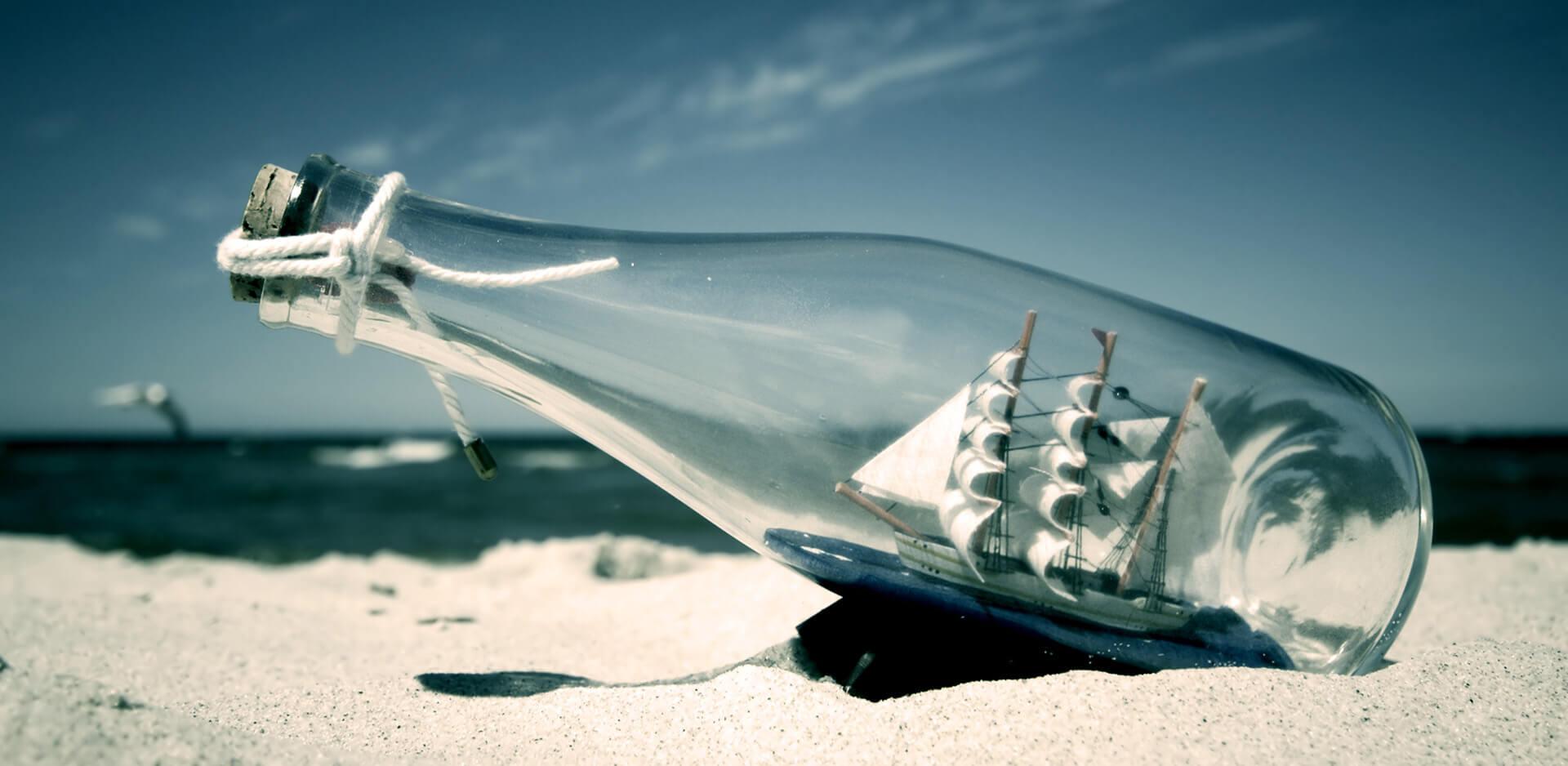 Model plachetnice v láhvi ležící na písečné pláži.