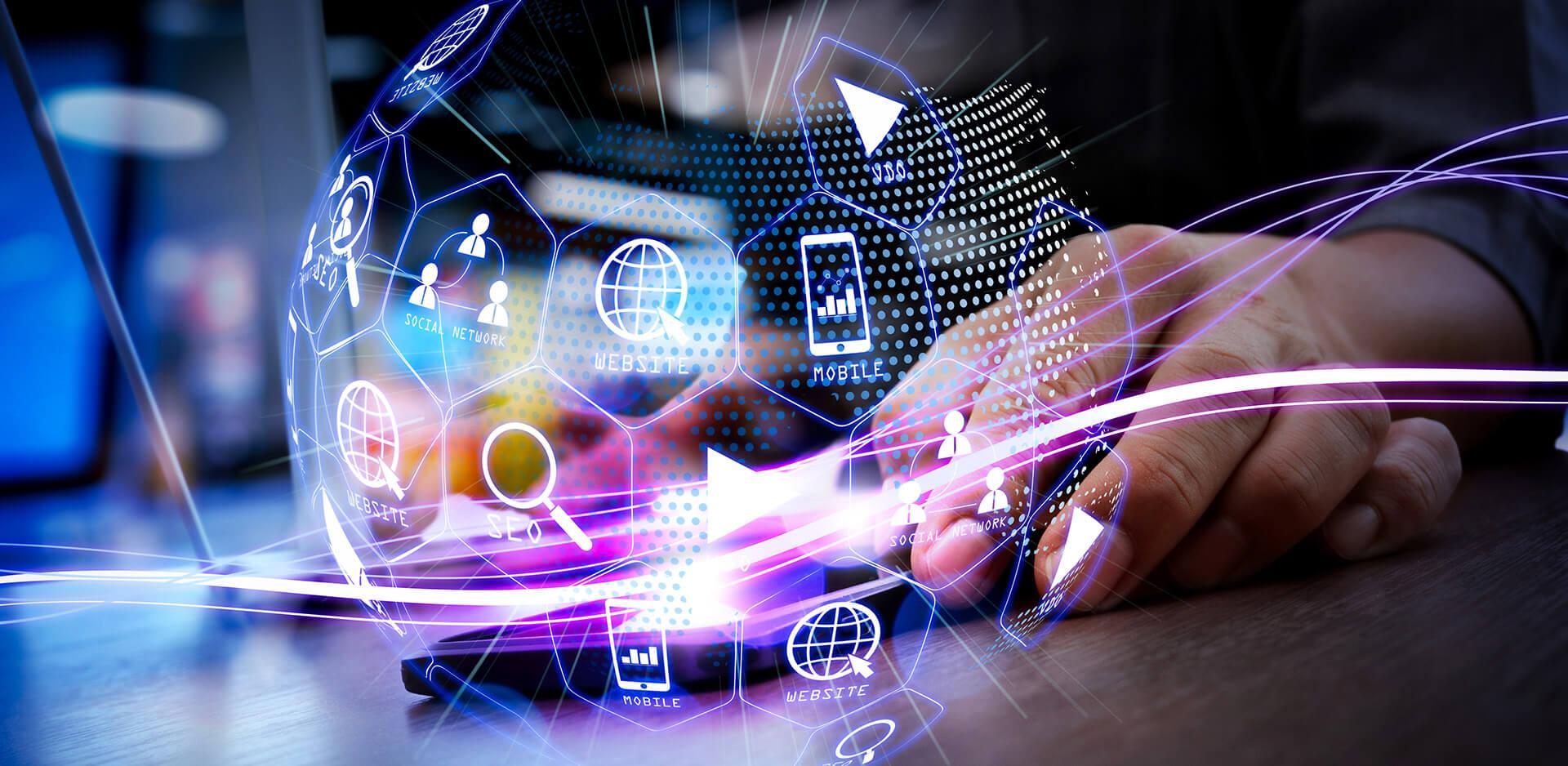 Virtuální koule obsahující symboly digitálního světa s rukou v pozadí