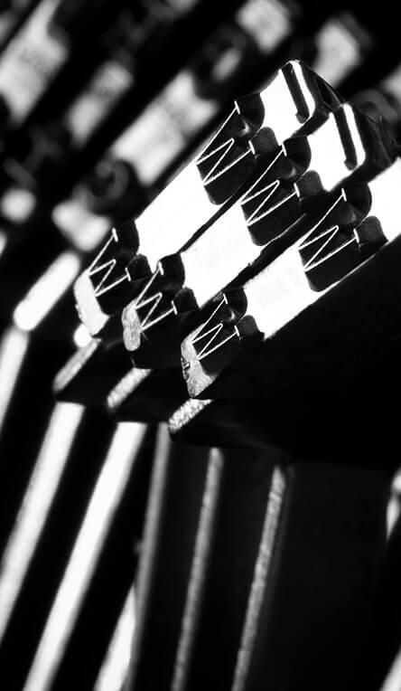 Černobílá fotografie úderníků psacího stroje s písmenem w.