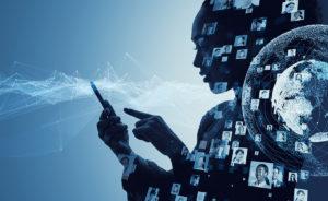 Silueta ženy držící mobil. Kolem ní je mnoho fotek tváří symbolizujících sociální sítě.